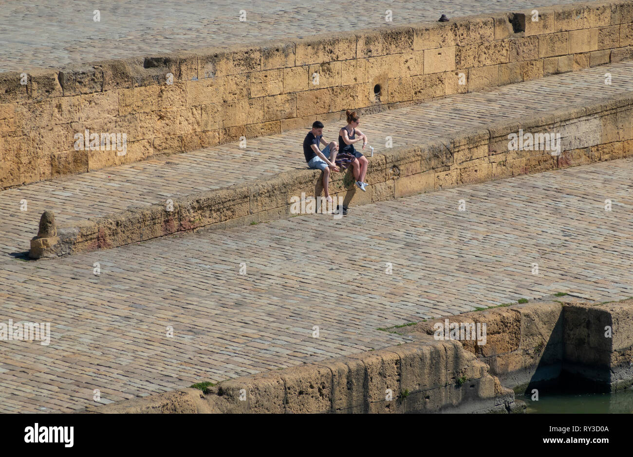 A young couple applying​ suntan lotion near the Guadalquivir river in Seville - Stock Image
