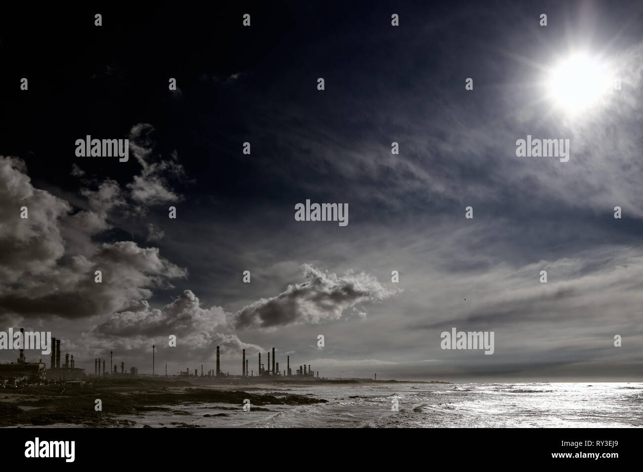 Oil refinery and powerplant near the sea with dramatic sky - Stock Image