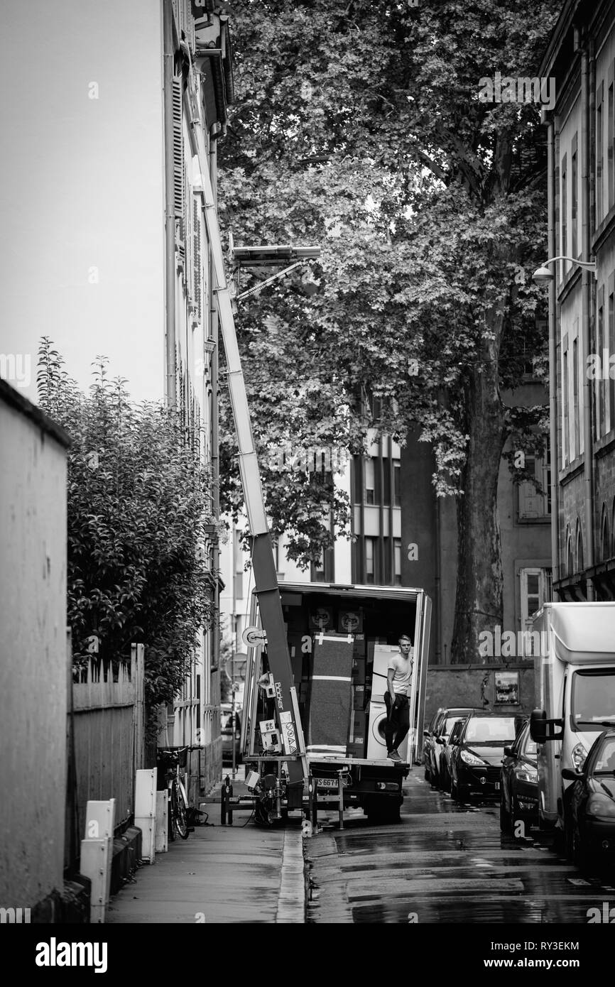 Strasbourg, France - Sep 12, 2017: Young male worker waiting for the hydraulic elevator boom to deliver another package during home relocation black and white - Stock Image