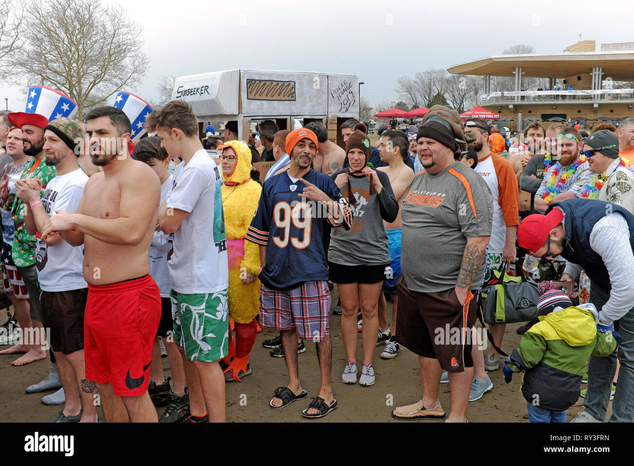 Participants in the 2019 Polar Plunge at Edgewater Park in Cleveland, Ohio, USA wait their turn to take a dip in the ice filled waters of Lake Erie. - Stock Image