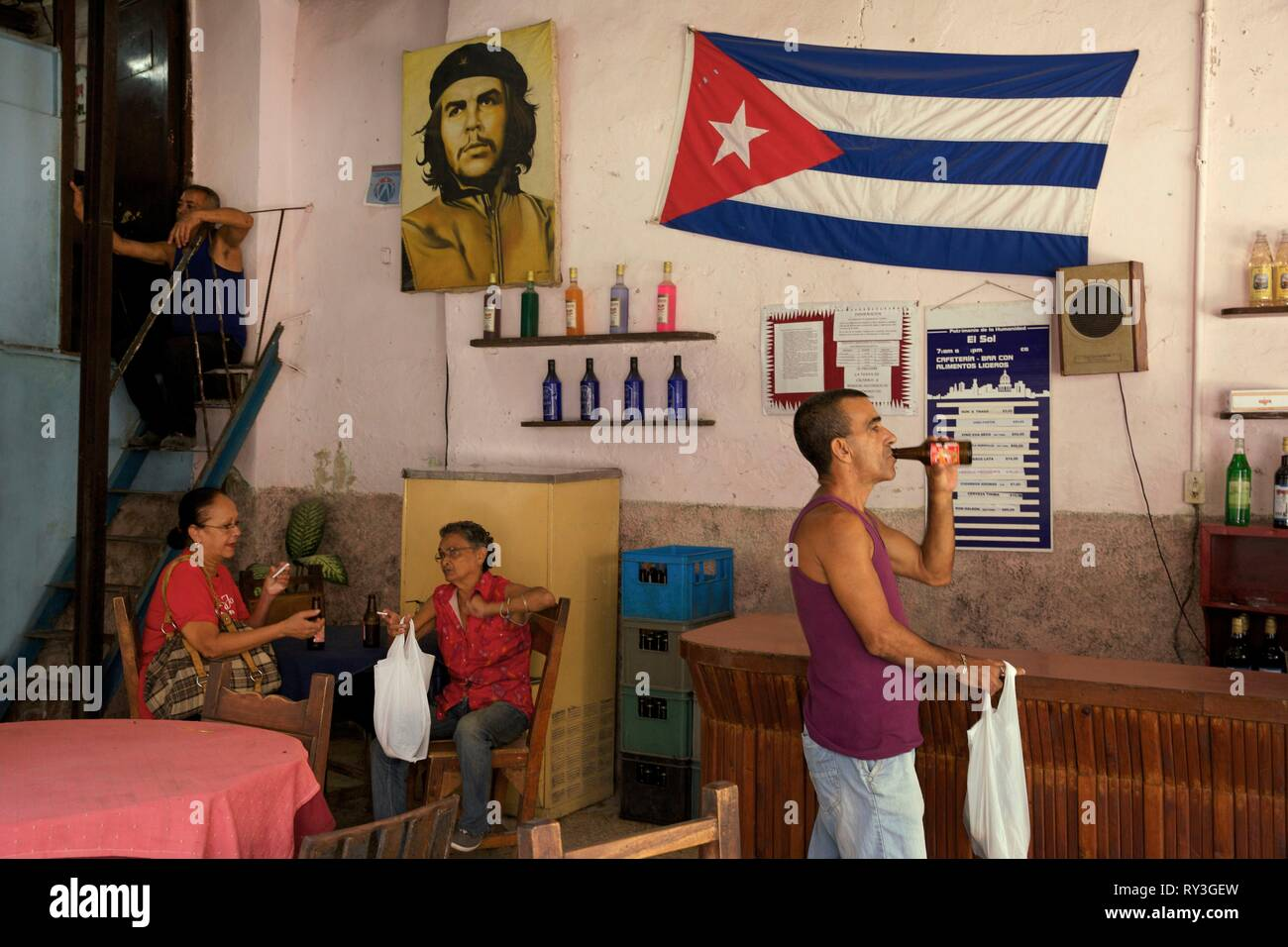 Cuba, La Havana, old Habana, listed as World Heritage by UNESCO, man drinking a beer and old women seated in a state bar decorated with a cuban flag and a portrait of Che Guevara - Stock Image