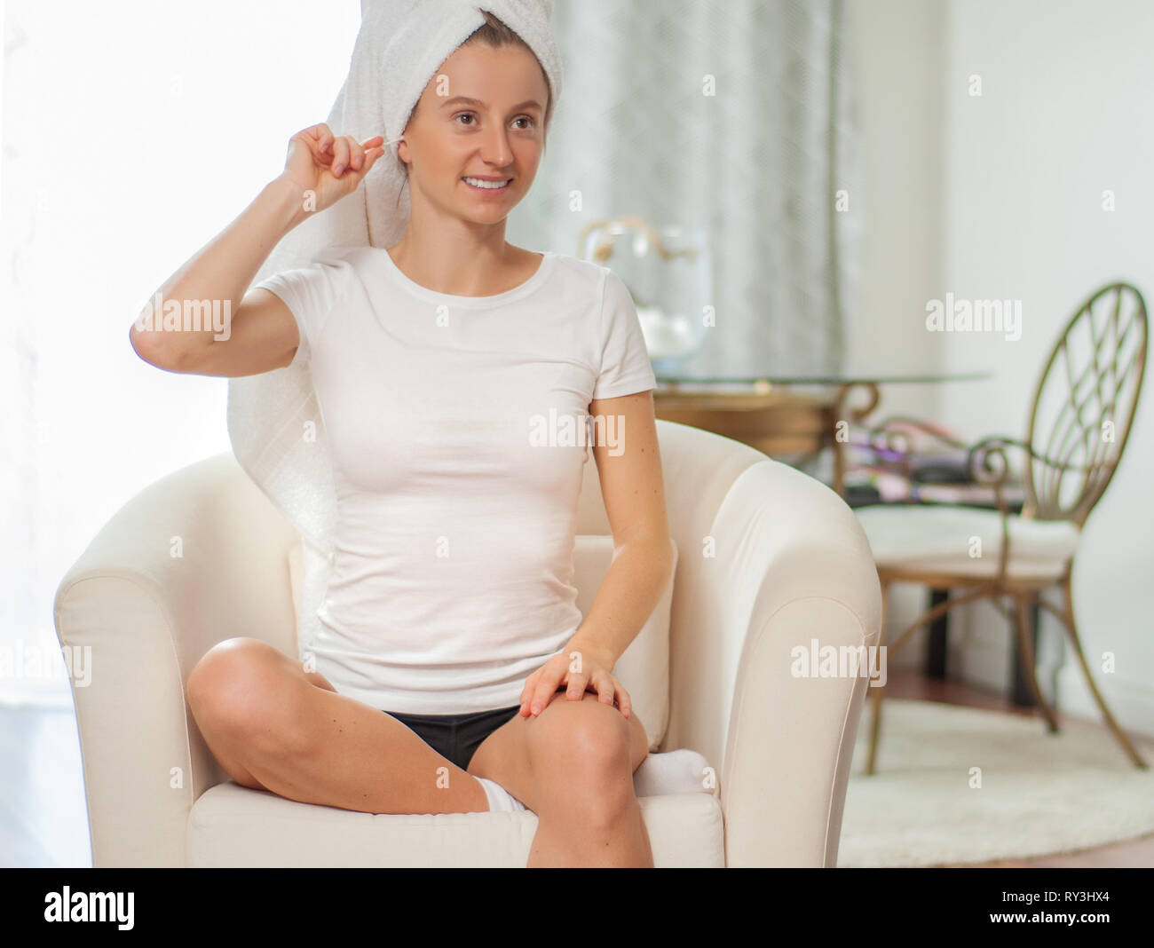 Young woman using a stick of cotton swab for ears cleaning. - Stock Image