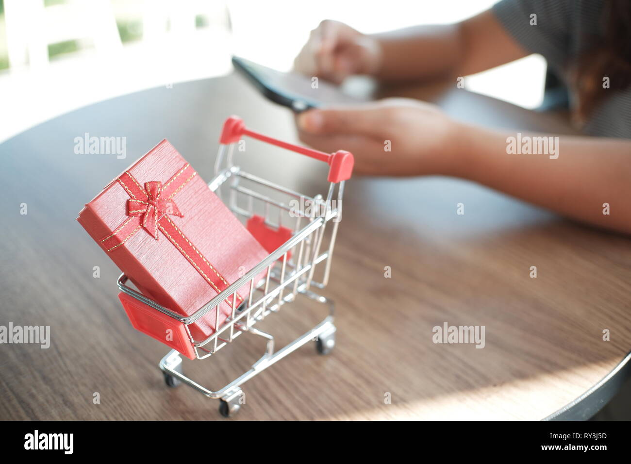 red gift box on shopping cart with women using mobile phone - Stock Image