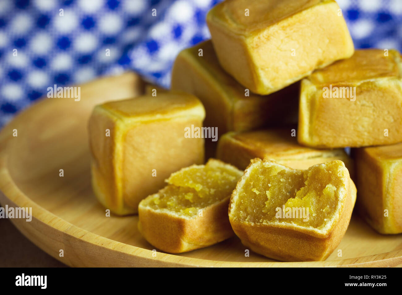 Closeup chinese cakes dice shaped are placed on a brown wooden table and have blue patterned tablecloths. - Stock Image