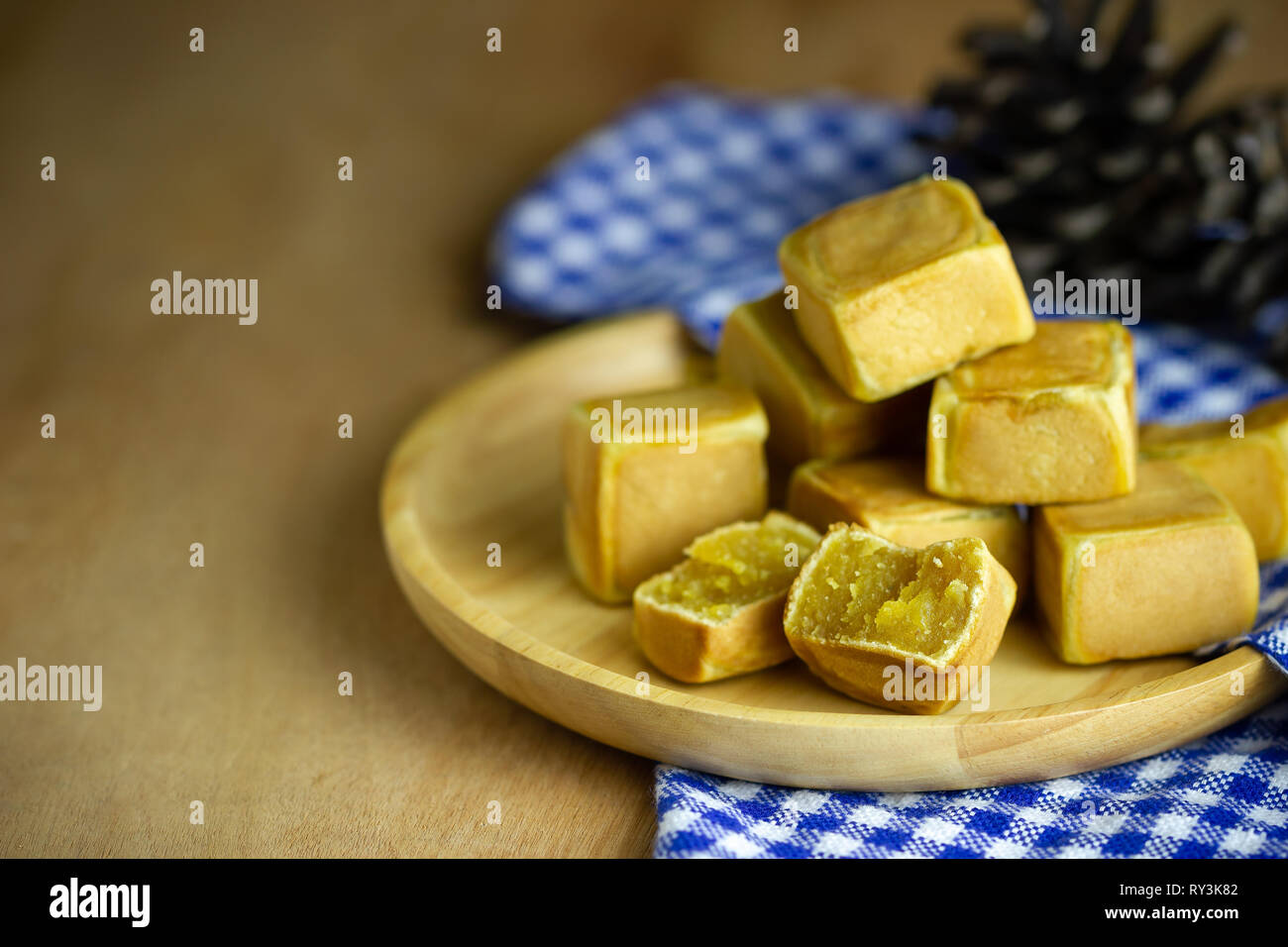 Chinese cakes dice shaped and dry pine flower are placed on a brown wooden table and have blue patterned tablecloths. - Stock Image