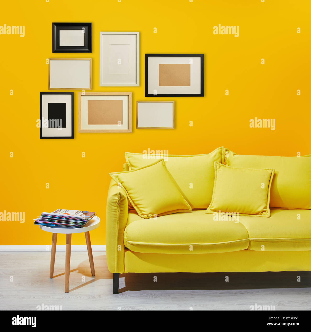 Picture of: Coffee Table Standing Near Modern Yellow Sofa Near Decorative Frames Hanging On Wall Stock Photo Alamy