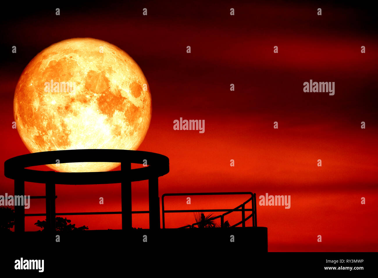 blood moon back over silhouette cycle on roof of building and night red sky cloud, Elements of this image furnished by NASA - Stock Image