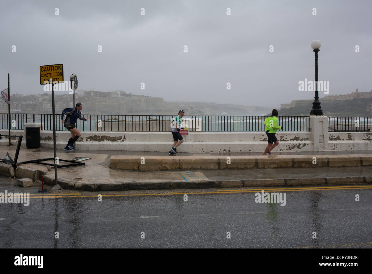 Runners during wild, stormy weather and flooding, in Sliema, Malta, 24 February 2019. - Stock Image