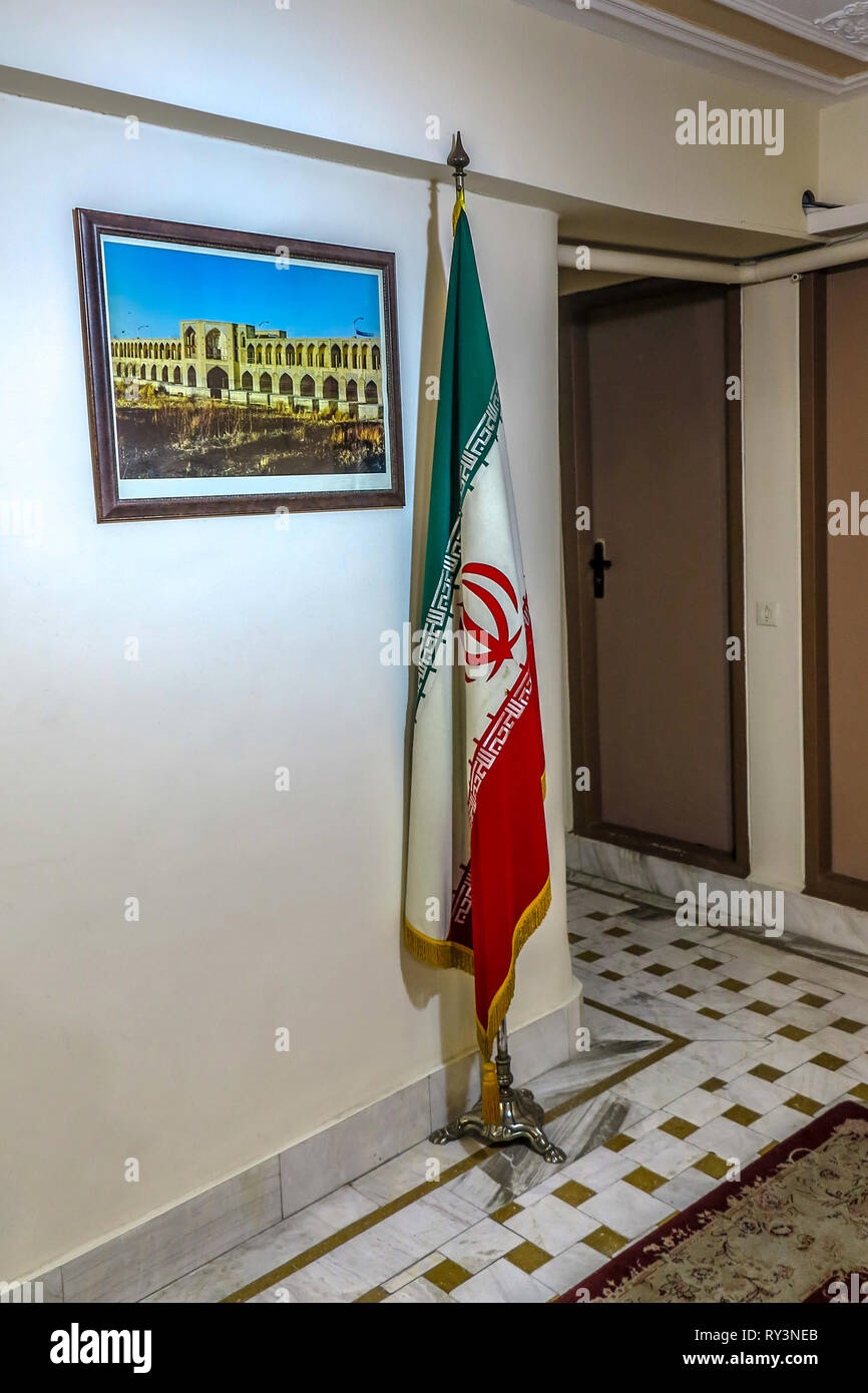 Iranian Flag Standing Still on a Flagpole in a Indoor Corridor with Image of Isfahan - Stock Image