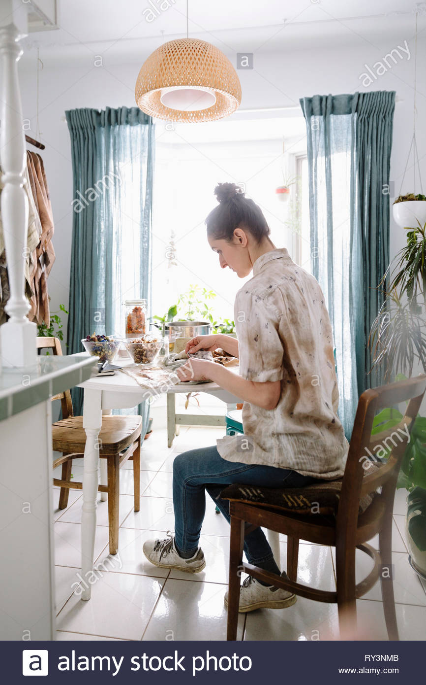 Female artist working at dining table - Stock Image