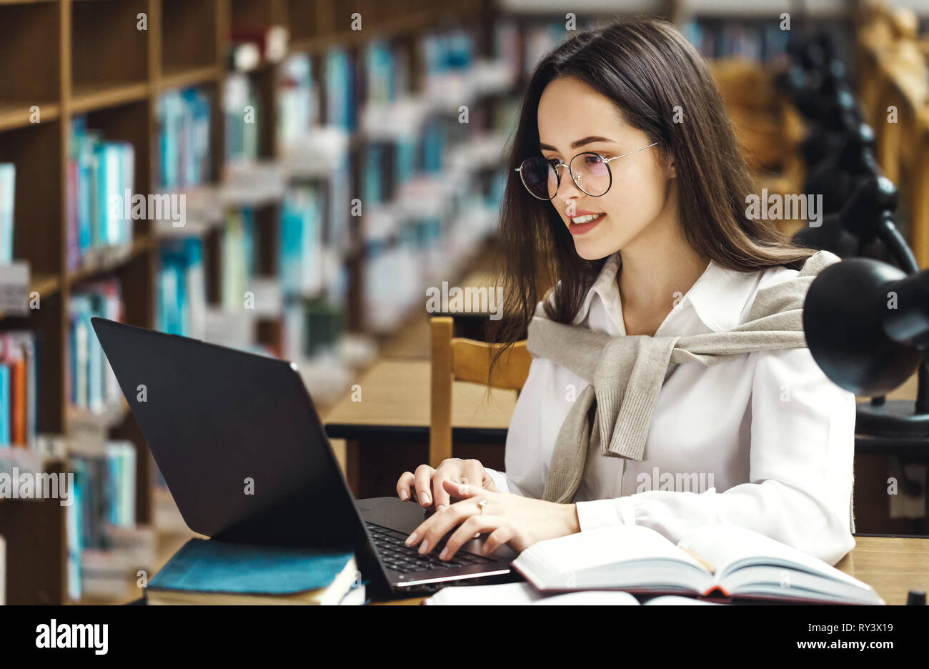 Brunette woman using laptop computer for startup project, researching information online Stock Photo