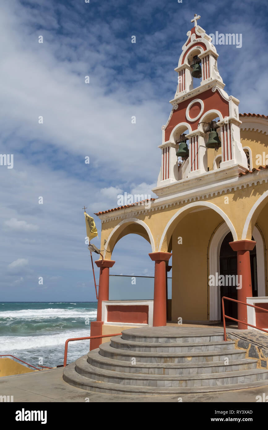 Coloroful small orthodox church of Ag. Fotini, located on the seaside. Foamy waves and horizon of the sea. Cloudy autumn sky. Rethymno, Crete, Greece. - Stock Image