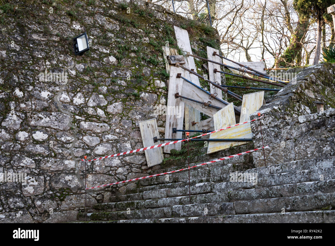 Antique stone wall with struts to prevent damages and falling stones - Stock Image