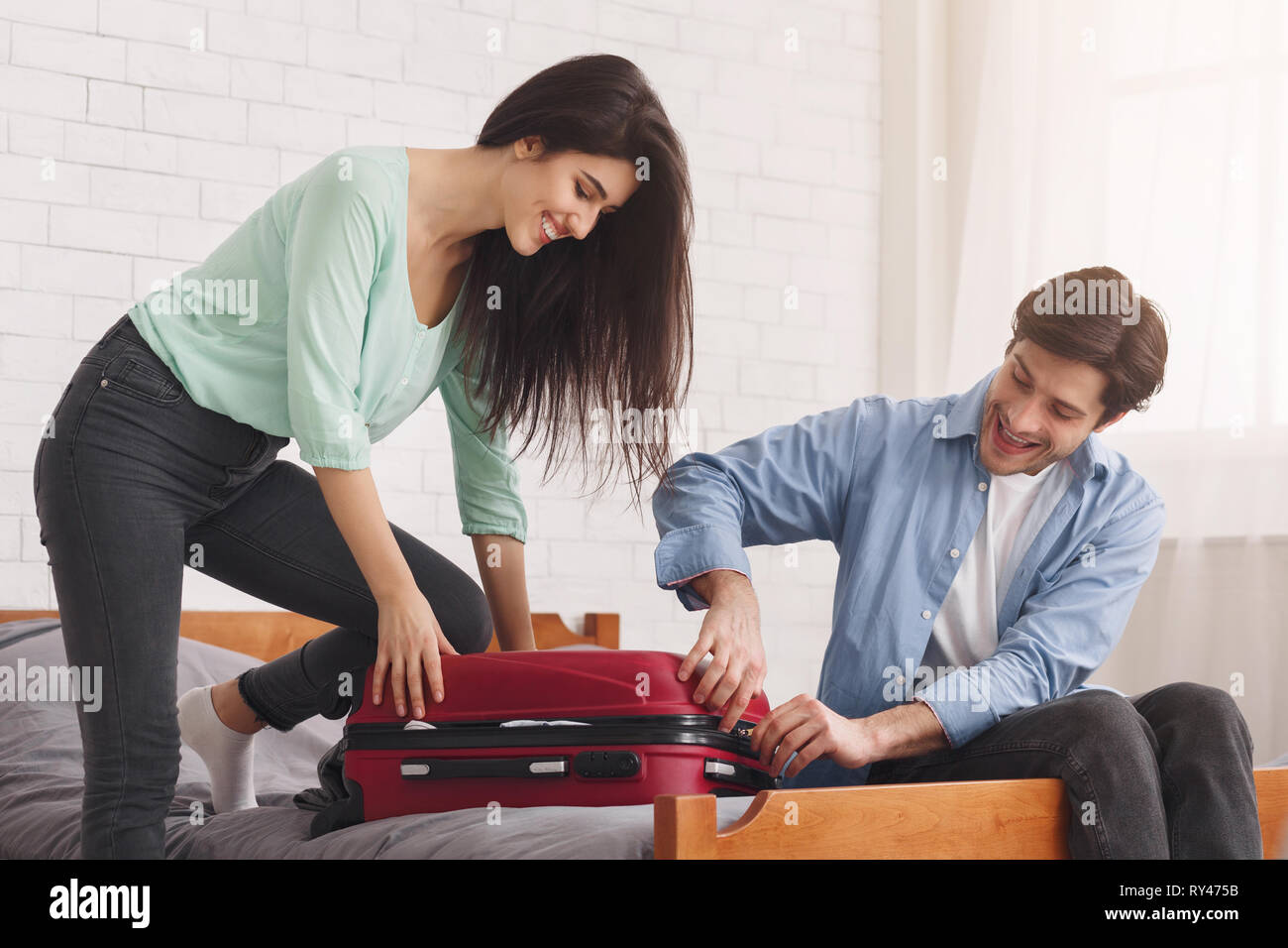 Couple closing full suitcase, preparing for vacation - Stock Image