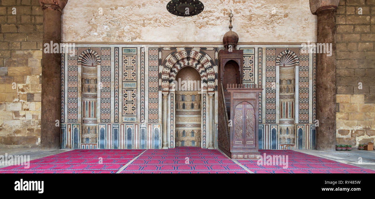 Colorful decorated marble wall with engraved Mihrab (niche) and wooden Minbar (Platform) at the Mosque of Al Nasir Mohammad Ibn Qalawun, situated in t - Stock Image