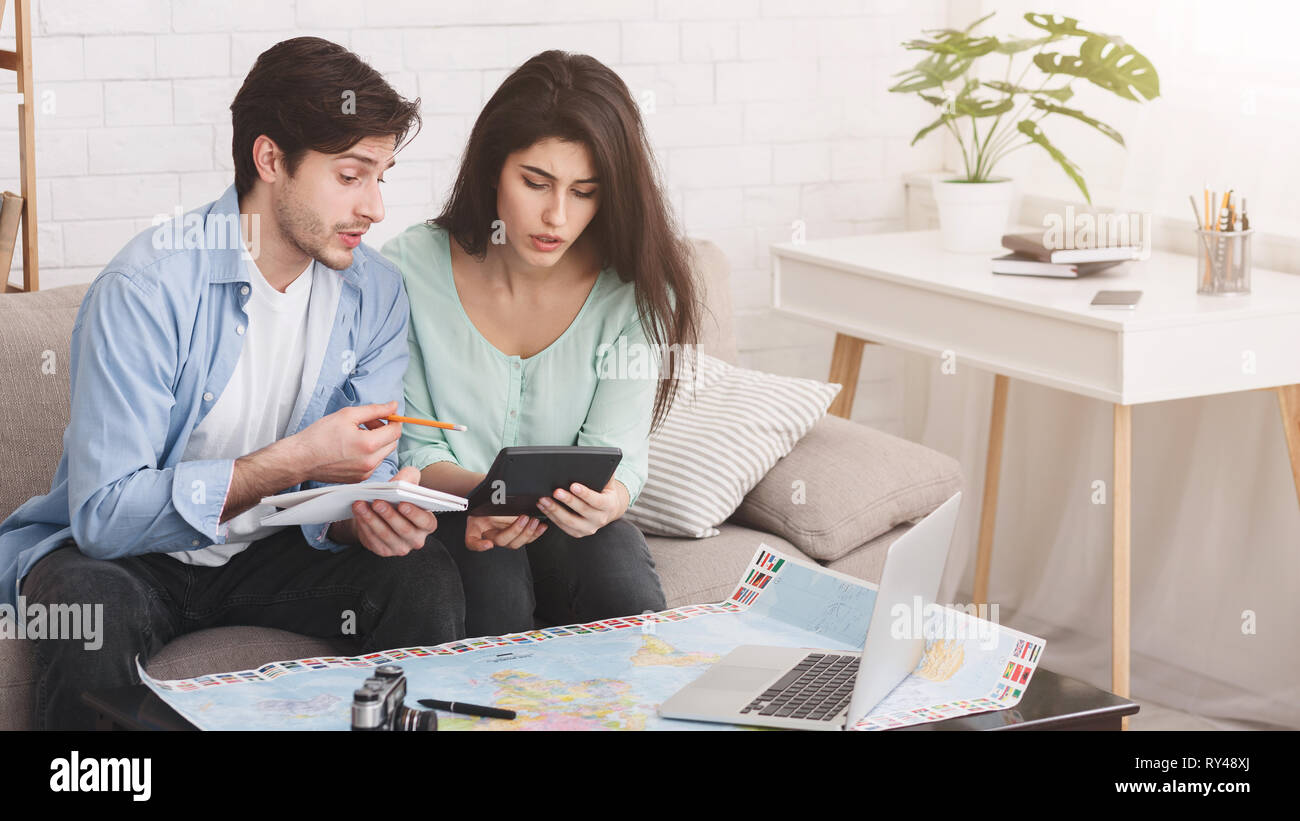 Couple counting finances for vacation, planning journey Stock Photo