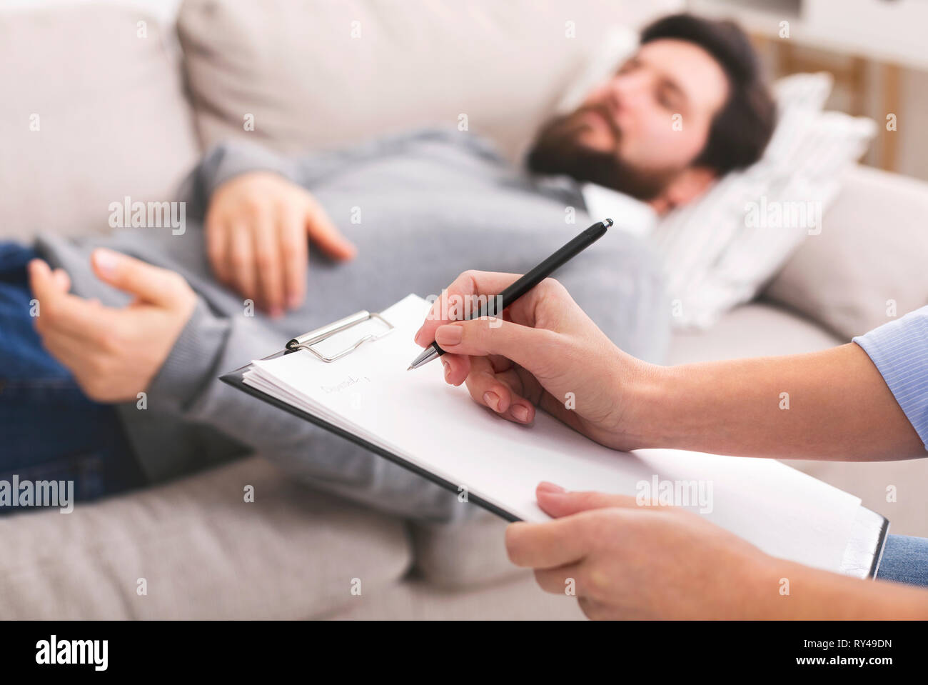 Patient lying on sofa at pcychological therapy - Stock Image