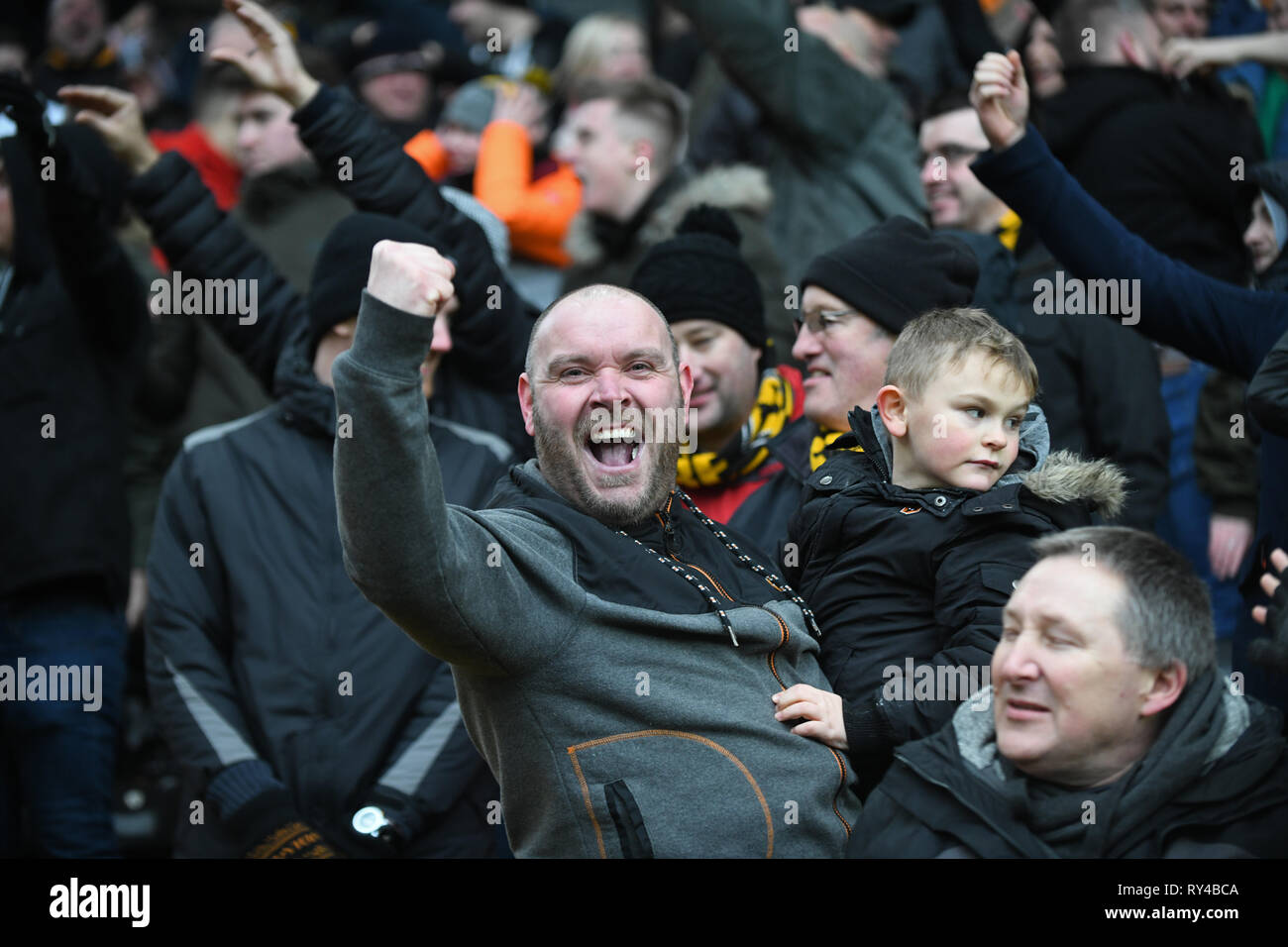 Football supporters father and son celebrating at football match - Stock Image