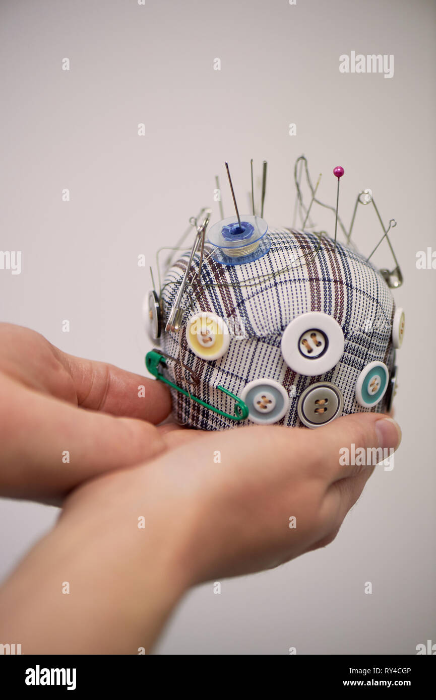Plaid pin cushion in the hands of seamstresses.Handmade, sewing. - Stock Image