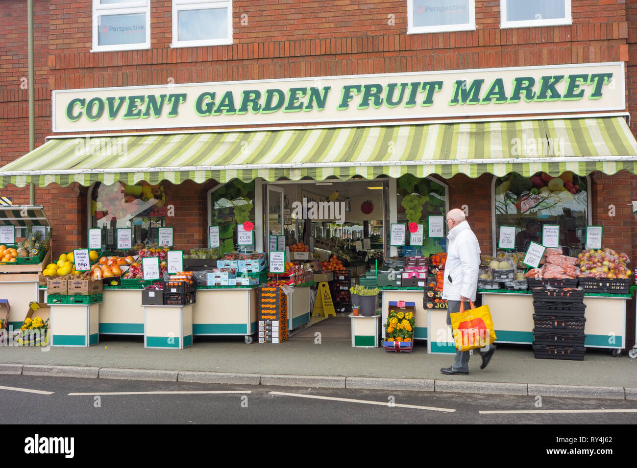 Traditional high street fruit and vegetable greengrocers shop with boxes and crates of fresh produce outside on the pavement in Oswestry Shropshire - Stock Image