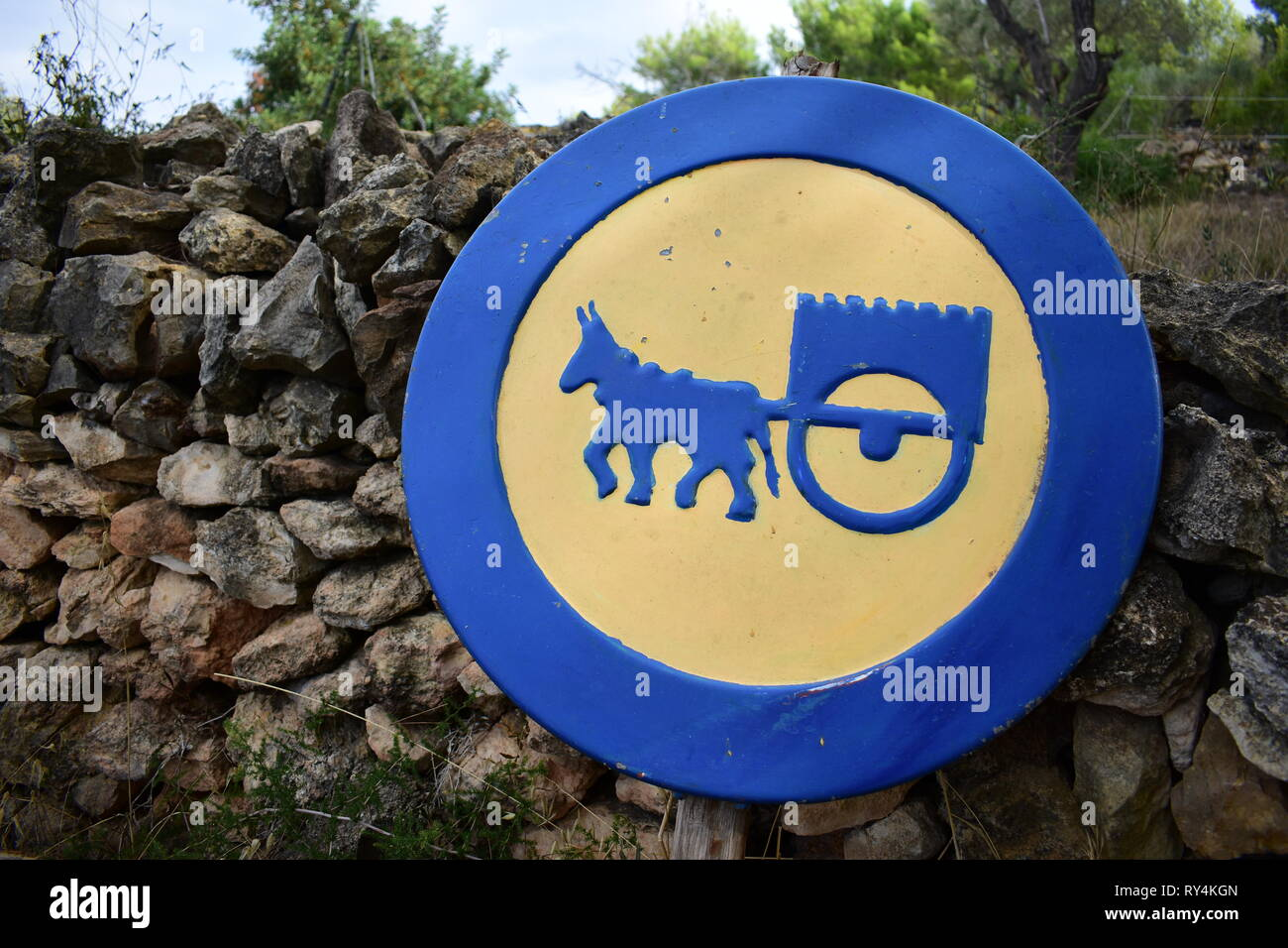 Warning sign in blue and yellow Attention donkey carts on a spanish farm - Stock Image