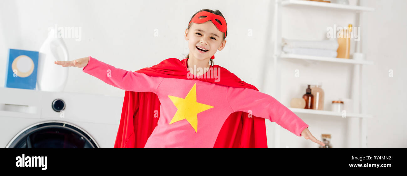 panoramic shot of child in red homemade suit with star sign having fun in laundry room - Stock Image