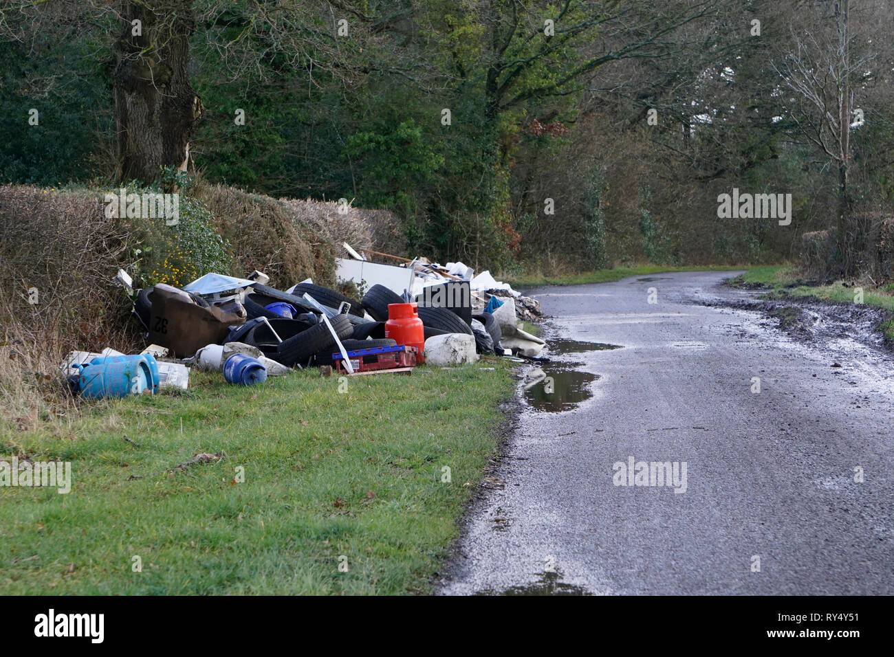Fly-tipping or illegal waste dumping in a country lane in the UK - Stock Image