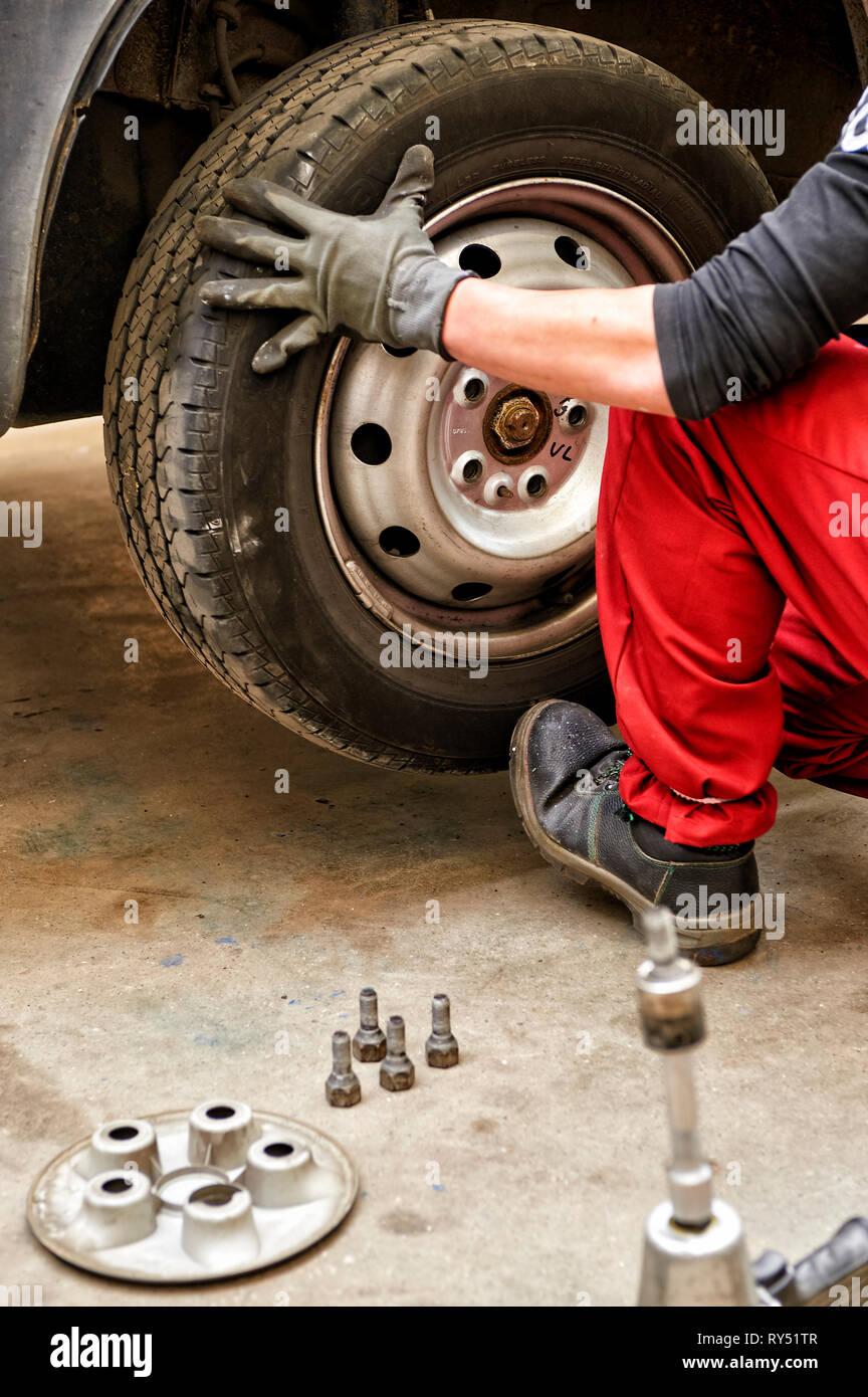 Auszubildender setzt ein Rad auf die Achse eines Autos. Er macht eine Radwechsel, Im Vordergrund stehn, Befestigungsschrauben. - Stock Image