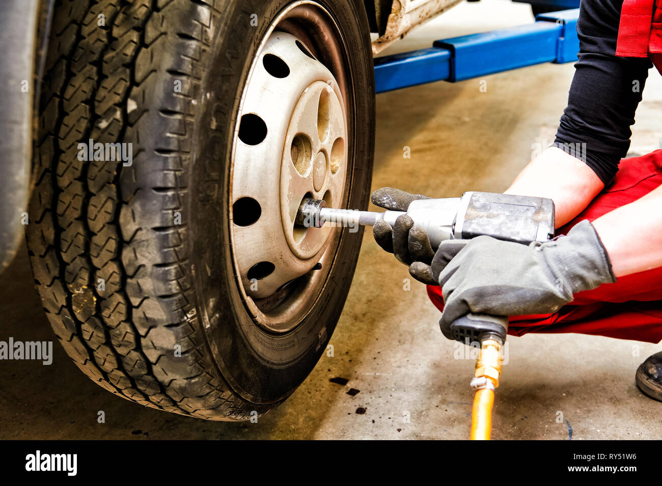 Auszubildender schraubt ein gewechseltes Rad eines Autos wieder an oder ab. Mit einem Pressluftschrauber. Stock Photo