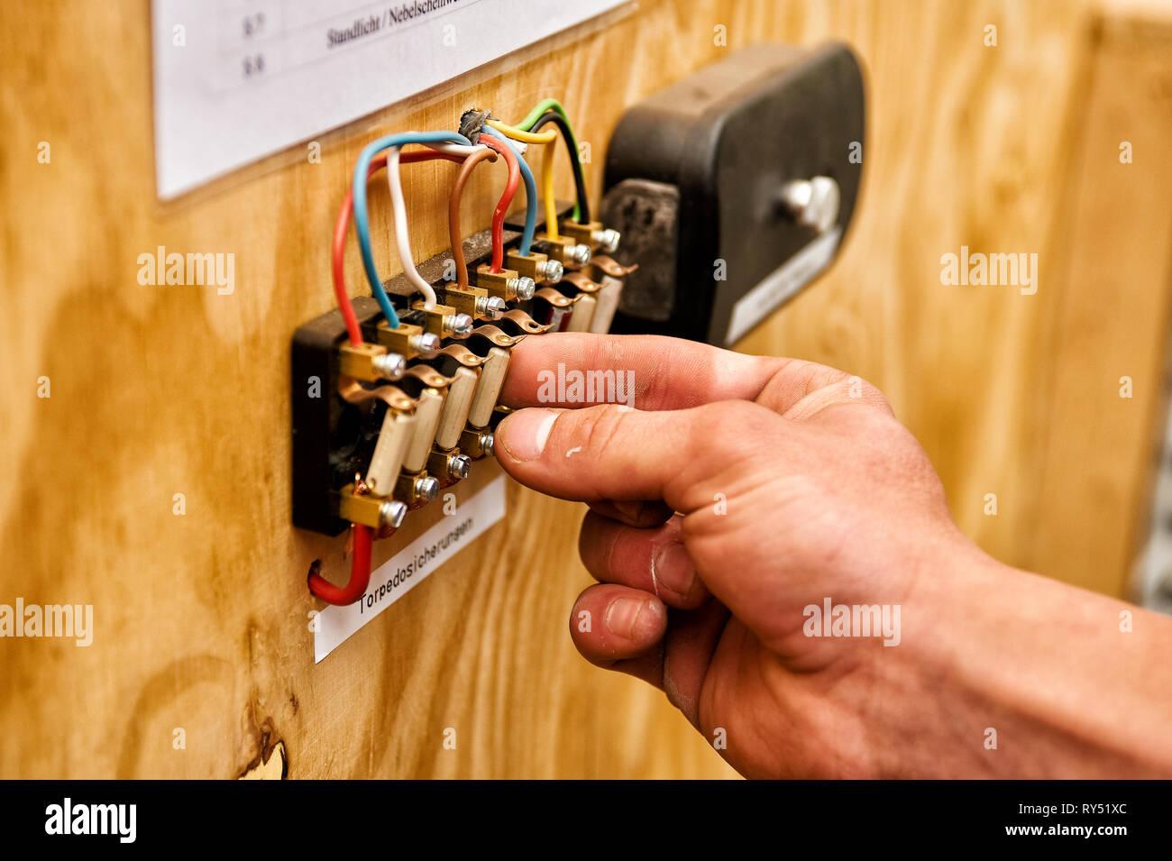 Auszubildender zum KFZ Mechaniker / Mechatroniker wechselt an einer Schautafel eine Torpedosicherung aus. - Stock Image