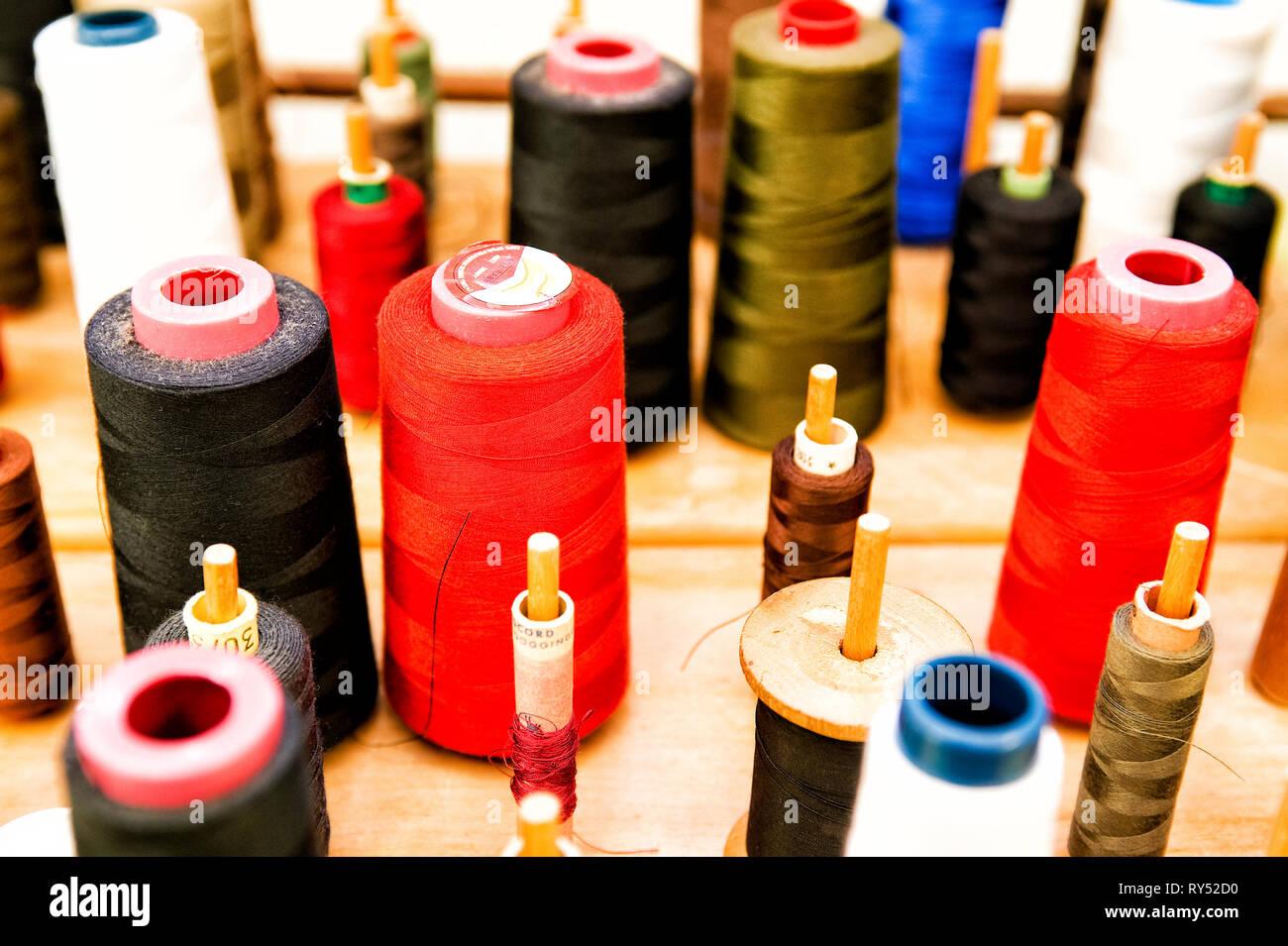 Nahaufnahme auf Rollen mit Naehgarn in unterschiedlichen Farben. - Stock Image