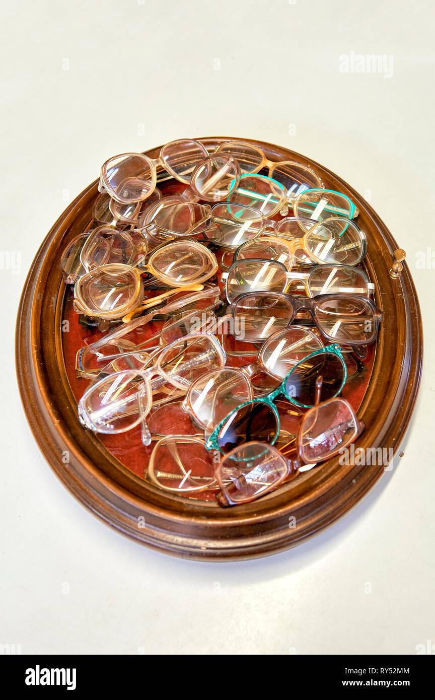 Auf einem Bilderrahmen liegen viele verschiedene Brillengestelle in einem Gebrauchtwarenlgeschaeft. - Stock Image