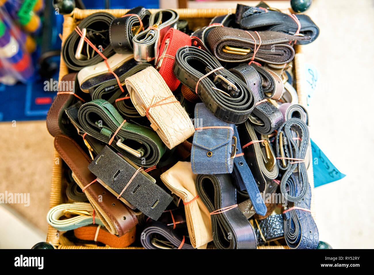 In einem Korb liegen verschiedenste, ordentlich, zusammengerollt Guertel. - Stock Image
