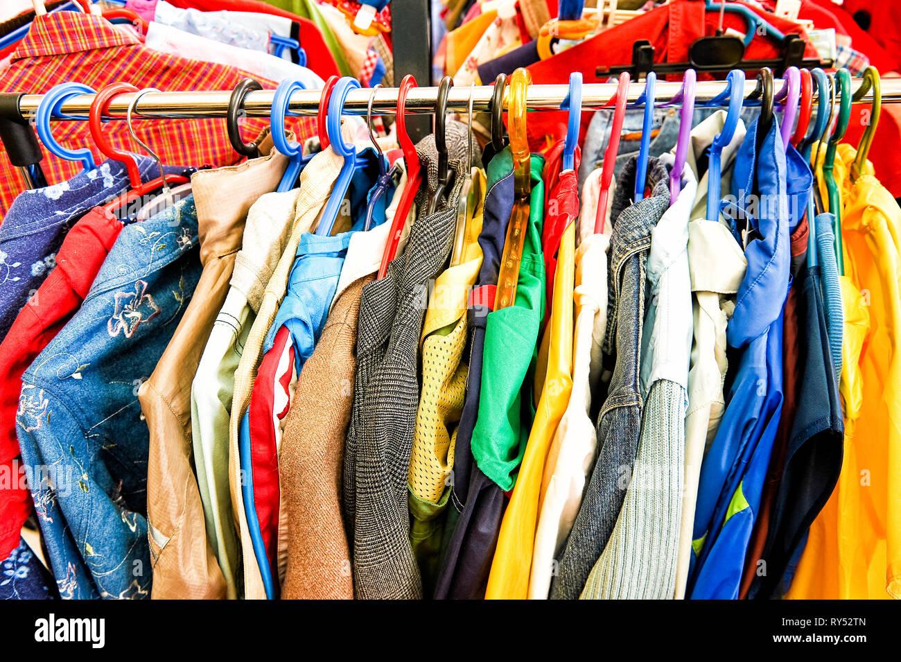 Auf einer Kleiderstange haengen buten Damen- und Herrenoberteile. - Stock Image