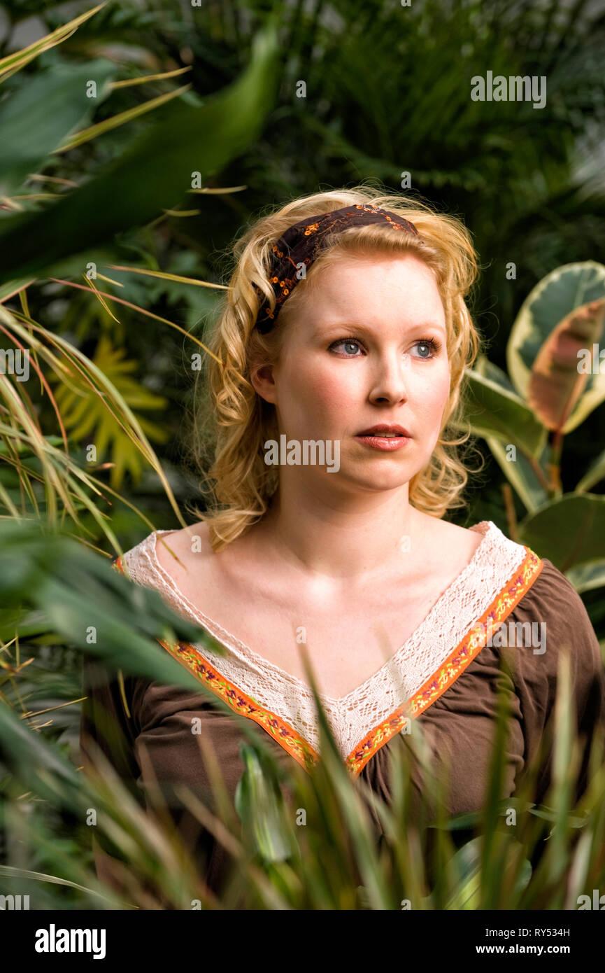 Eine junge Frau steht zwischen Palmen und schaut nachdenklich. - Stock Image
