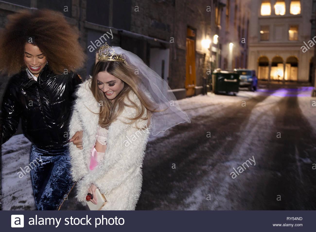 Bachelorette and friend walking on snowy urban street - Stock Image