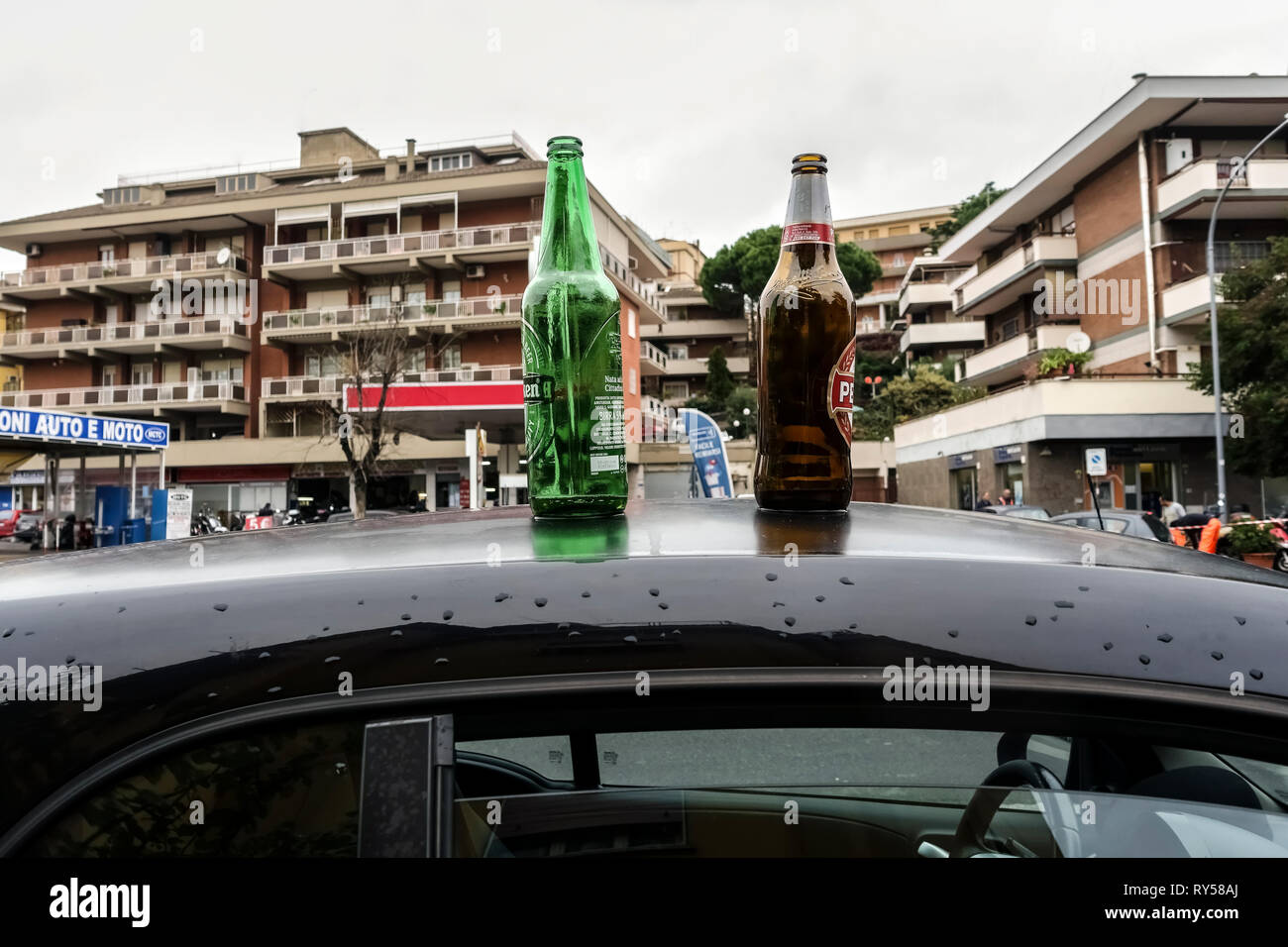 Two empty beer bottles on a car roof parcked in the street. Alcohol addiction concept. Blurred background. - Stock Image