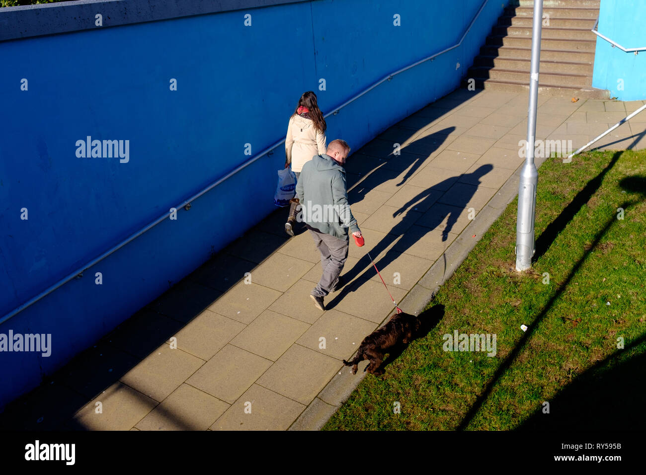 A man with dog on lead casts a shadow as he walks through underpass fort william town center - Stock Image