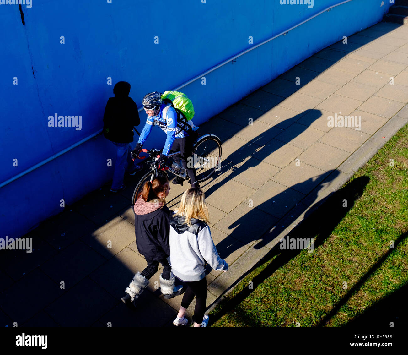 A cyclist enters underpass passing other pedestrians as they leave into bright sunshine,lochaber fort william - Stock Image