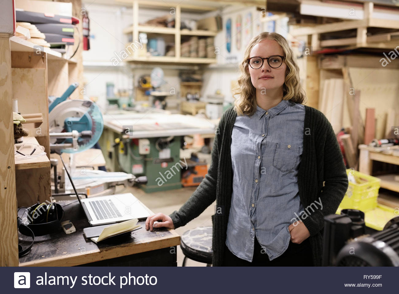 Portrait confident female artist in woodworking workshop - Stock Image