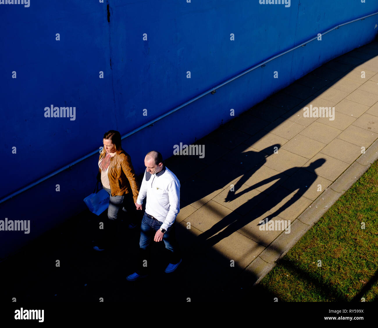 A couple holding hands cast their shadow behind them as they enter underpass in bright sunshine, fort william high street lochaber Stock Photo