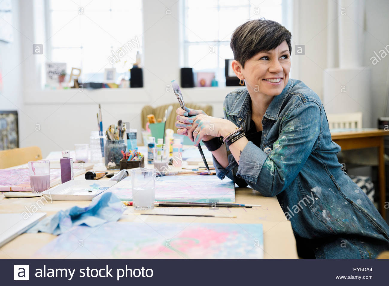 Smiling female artist painting in studio - Stock Image