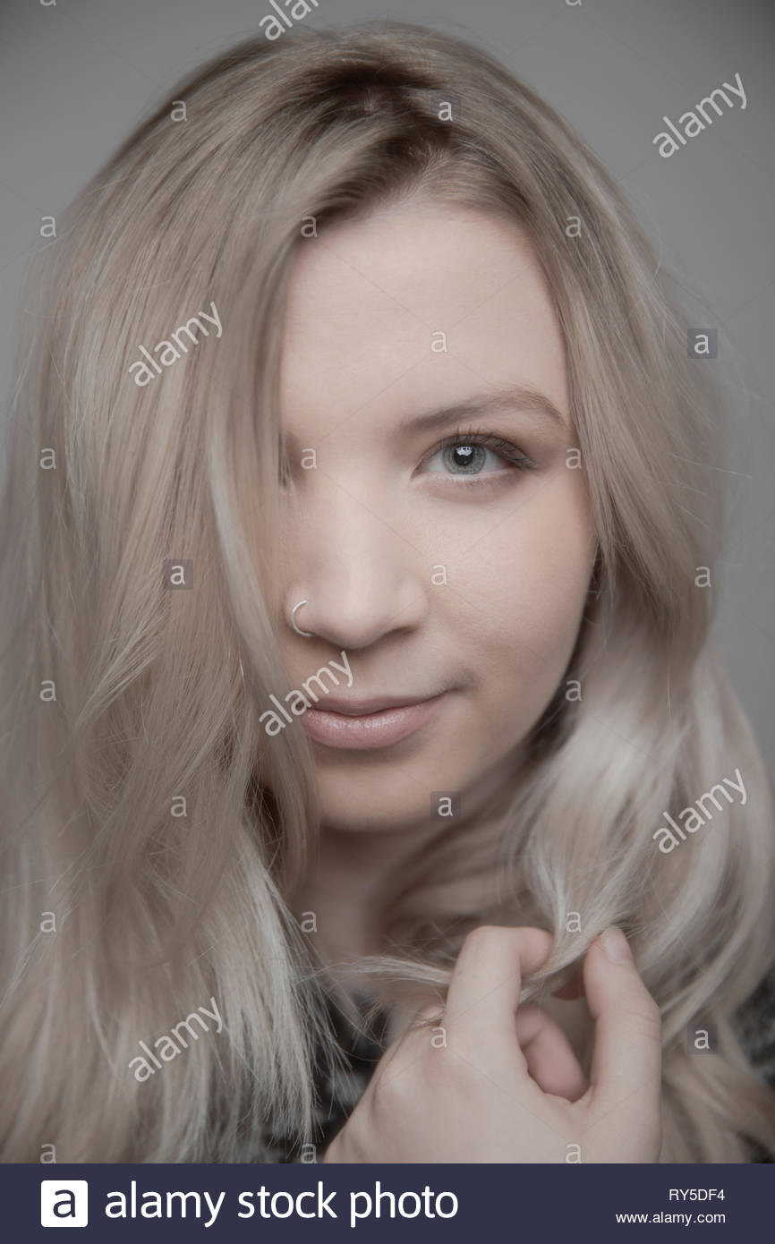 Close up portrait confident beautiful young blonde woman with nose ring and blue eyes - Stock Image