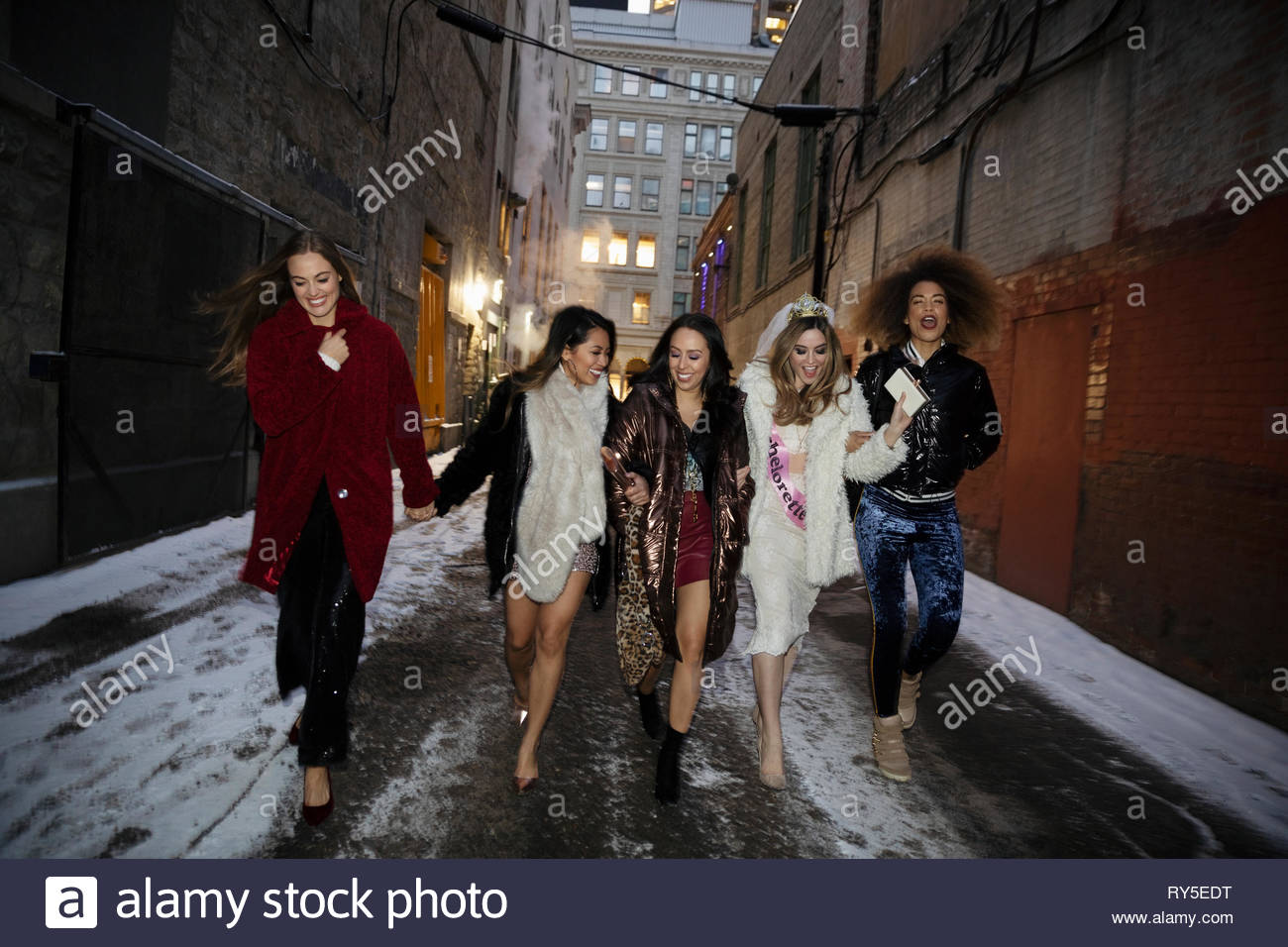 Bachelorette and friends walking along snowy urban alley - Stock Image