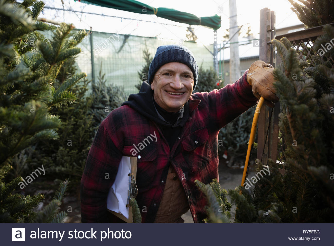 Portrait happy worker at christmas tree market - Stock Image