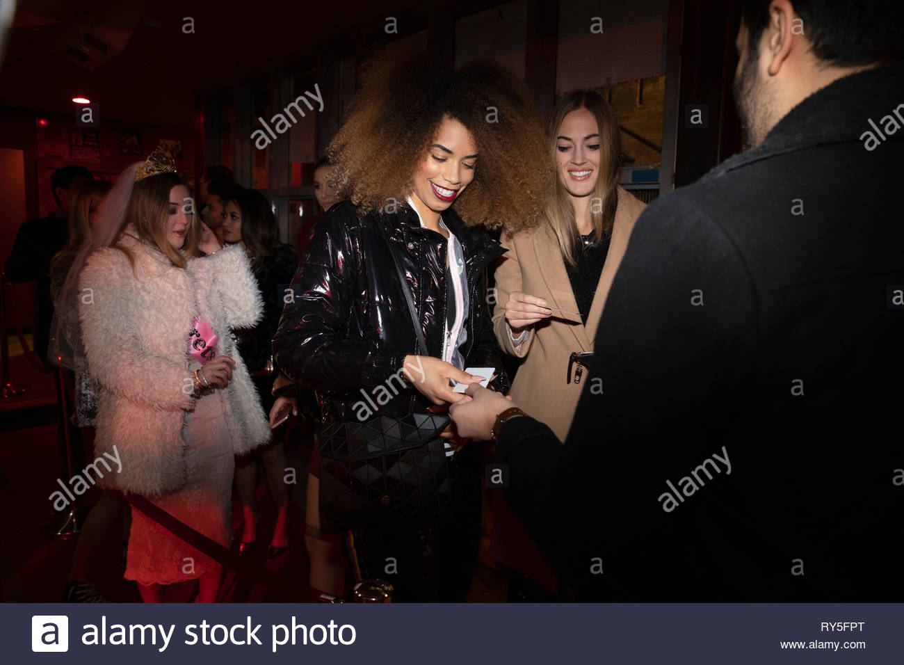 Women showing IDs to bouncer in nightclub queue - Stock Image