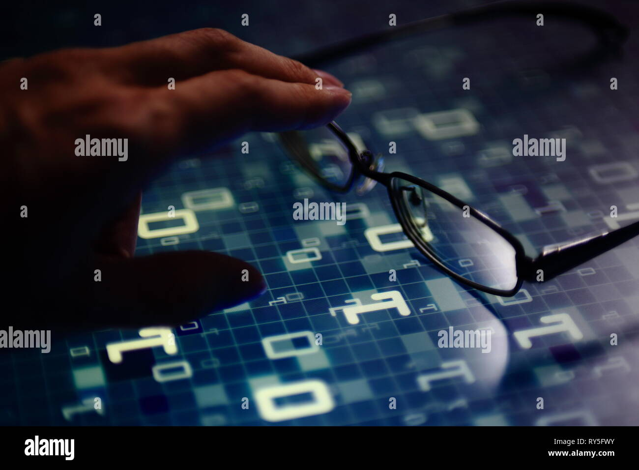 hand reaching for glasses on digital led displaying multiple layers of binary code computer data matrix. big data analytics and digital language conce - Stock Image