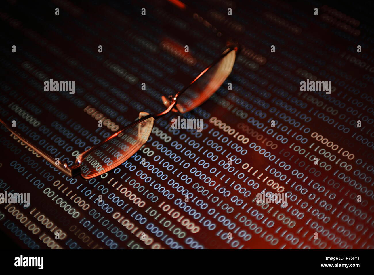 computer hacker. red dangerous code breach into red binary code with glasses place over led panel. virus, cyber threat and computer internet system fa - Stock Image