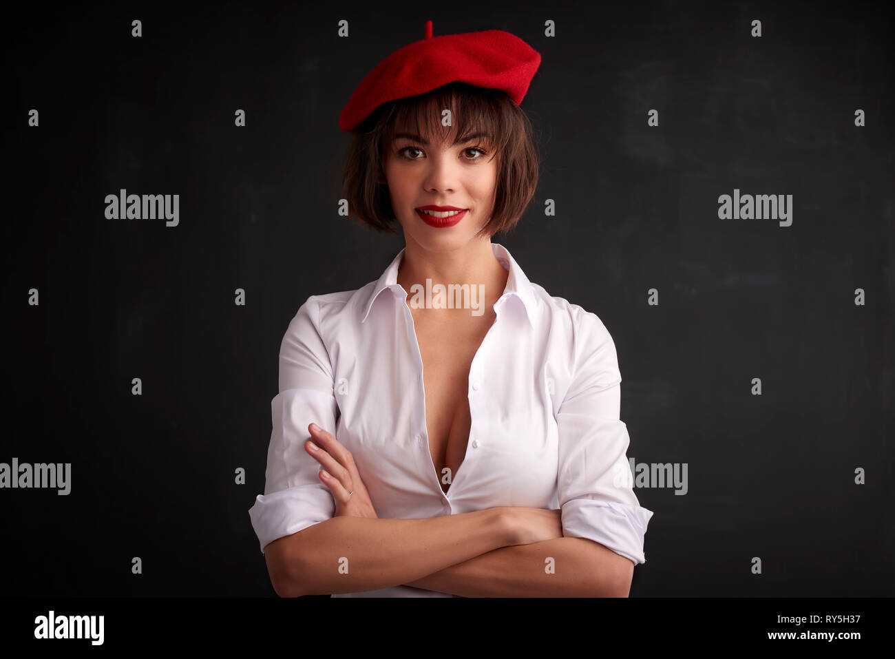 31fb3b01c4589 Portrait shot of beautiful young woman with folded arms wearing red beret  and white shirt while