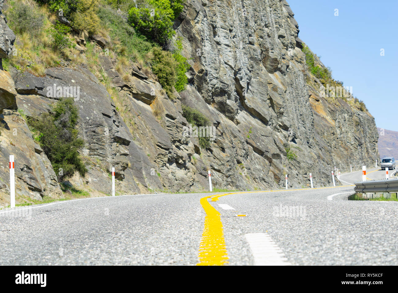 South Island curving highway with yellow no over-taking line through hills - Stock Image